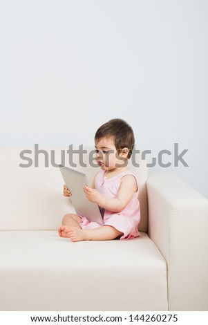 Sweet baby reading on a tablet