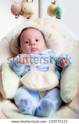 sweet baby seated on a rocking chair - stock photo
