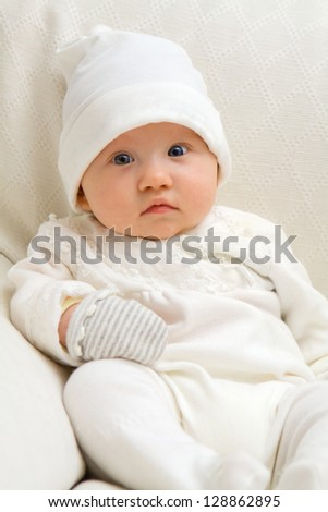 Sweet baby sitting on couch wearing white - stock photo