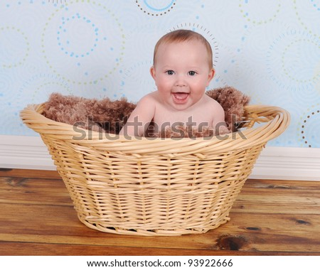 sweet baby sitting with big smile and bright eyes in wicker basket - stock photo