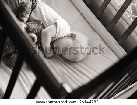 sweet baby sleeping in his crib with his teddy bear in black and white - stock photo
