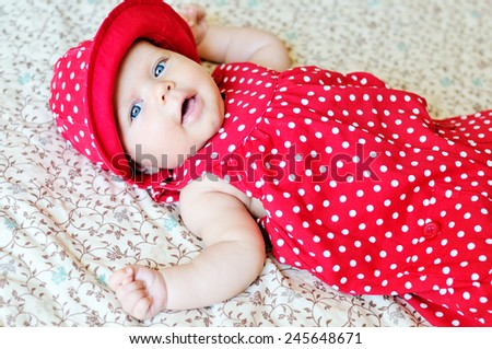 sweet baby wearing dotted dress and hat - stock photo