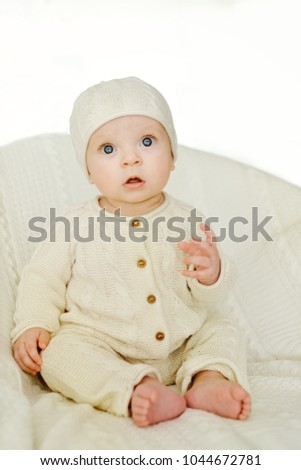 sweet baby wearing knitted suit is sitting on the chair