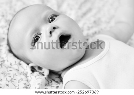 sweet baby with open mouth laying on the bed - stock photo