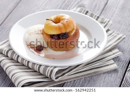 Sweet baked apple served with raisins and vanilla icecream. Homemade fruit dessert decorated with pinch of cinnamon. - stock photo