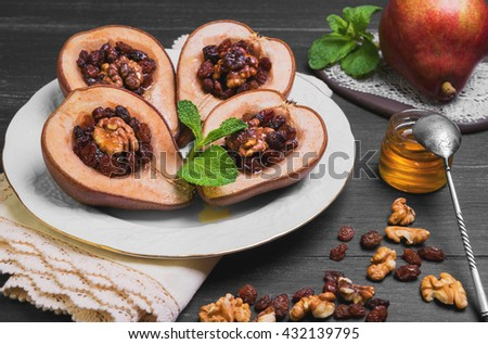 Sweet Baked pear halves with stuffing, ingredients for baked raisins, walnuts, honey, mint leaves, fresh pear, silver teaspoon, black wood background, white porcelain plate, ceramic board, lace doily - stock photo