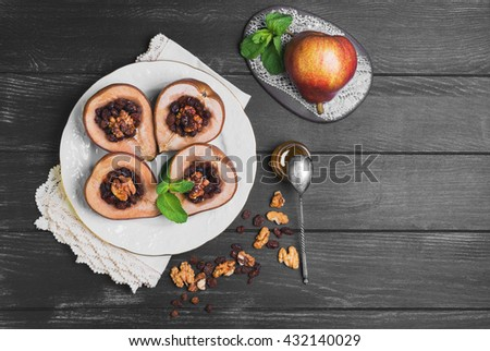 Sweet Baked pear halves with stuffing, ingredients for baked raisins, walnuts, honey, mint leaves, fresh pear, silver teaspoon, black wood background, white plate, ceramic board, lace doily, top view - stock photo