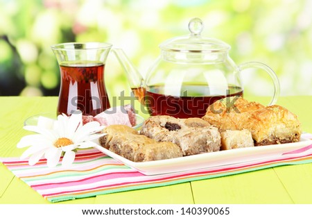Sweet baklava on plate with tea on table on bright background