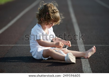 sweet beautiful little girl learning to tie shoelaces - stock photo