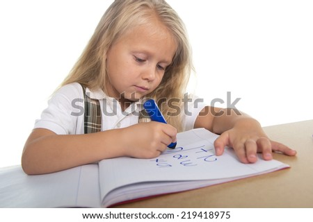 sweet beautiful little school girl with blonde hair sitting happy on desk drawing on notepad with marker in children education concept isolated on white background