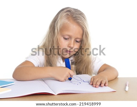 sweet beautiful little school girl with blonde hair sitting happy on desk drawing on notepad with marker in children education concept isolated on white background - stock photo