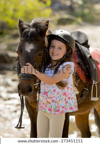 sweet beautiful young girl 7 or 8 years old hugging head of little pony horse smiling happy wearing safety jockey helmet posing outdoors on countryside in summer holiday - stock photo