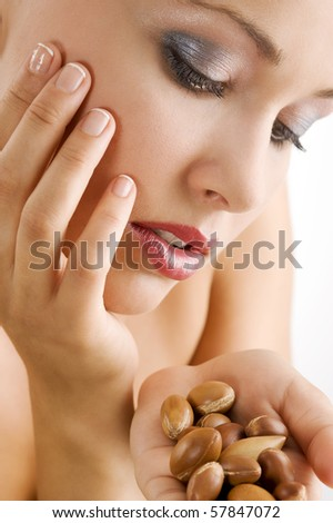 sweet beauty portrait of blond girl looking at some argan seeds on her hand - stock photo