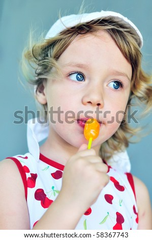 sweet blonde girl with lollipop in summer time - stock photo