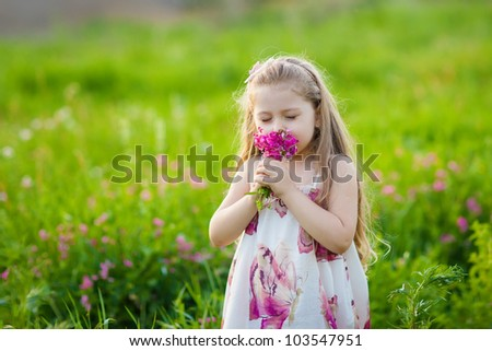Sweet blonde little girl smelling field flowers on the meadow - stock photo