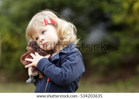 Sweet blonde little girl with blue eyes is hugging a favorite toy in the park in spring