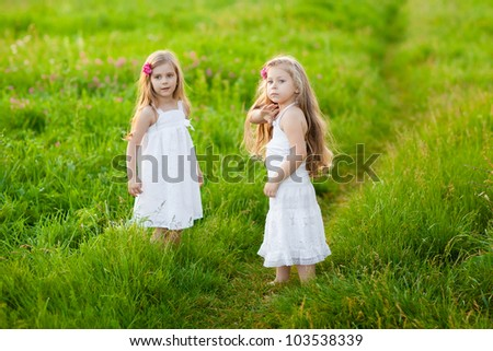 Sweet blonde little girls playing on the meadow - stock photo