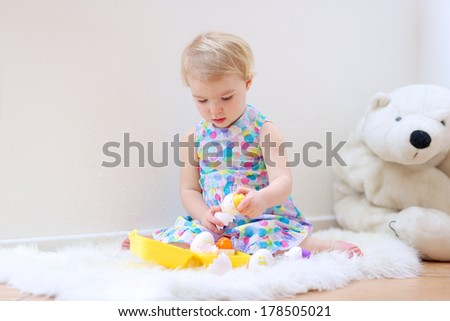 Sweet blonde toddler girl in beautiful dress playing indoors sorting colorful plastic eggs: Easter theme