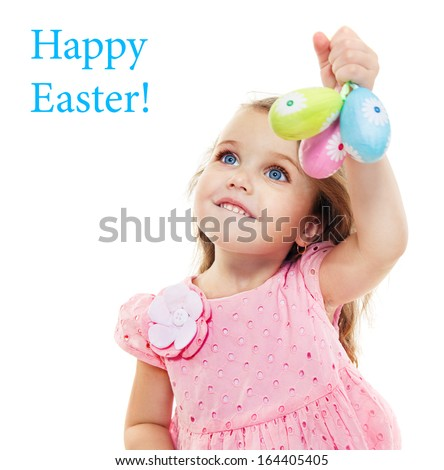 Sweet blue eyed little gil holding three eggs - symbol of Easter - stock photo