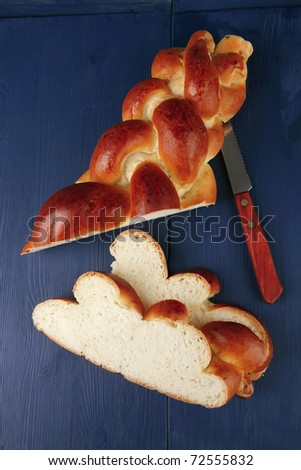 sweet bread : golden challah cuts over blue wooden plate - stock photo