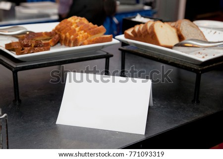 sweet bread loaf on plates with a blank sign on a counter