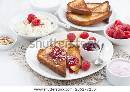 sweet breakfast - crispy toasts with raspberries, banana and jam, horizontal - stock photo