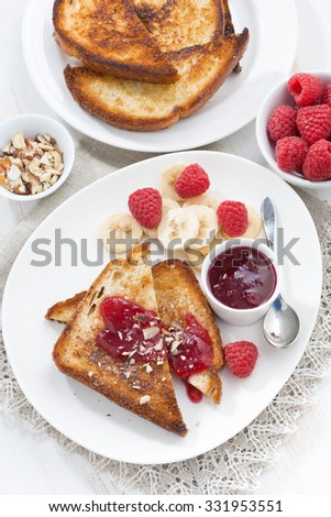 sweet breakfast - crispy toasts with raspberries, banana and jam, vertical, top view, close-up - stock photo