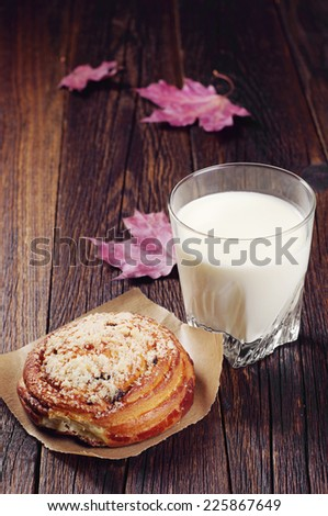 Sweet bun and glass of milk on old wooden table