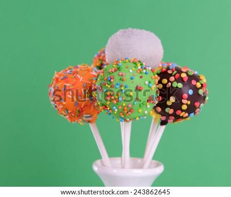 Sweet cake pops in vase on green background - stock photo