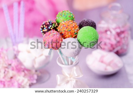 Sweet cake pops in vase on table on bright background - stock photo