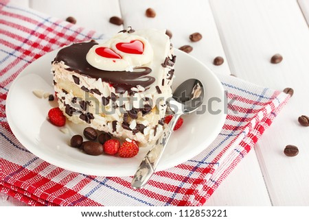 sweet cake with chocolate on plate on wooden table - stock photo