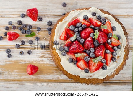 Sweet Cake with fresh berries on  wooden background. Top view - stock photo