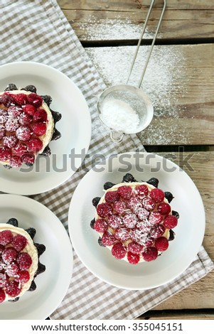 Sweet cakes with raspberries on light wooden background - stock photo