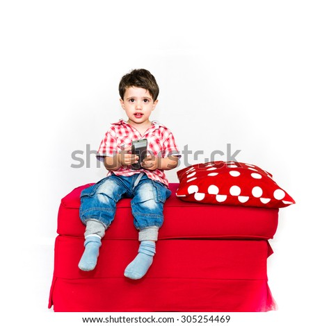 sweet caucasian child watching tv alone on a red sofa - stock photo