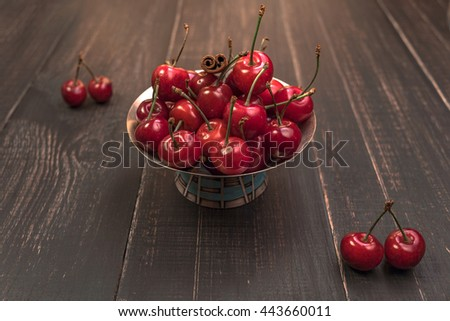 Sweet cherries in silver vase  on wood table at golden hour.