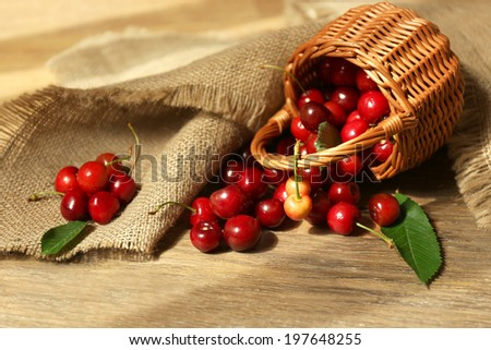 Sweet cherries in wicker basket on wooden table  - stock photo