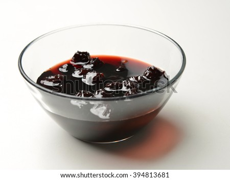 Sweet cherries jam in the transparent glass bowl on a white background - stock photo