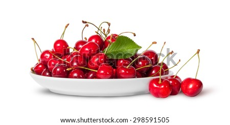 Sweet cherries with leaf on white plate and three near isolated on white background
