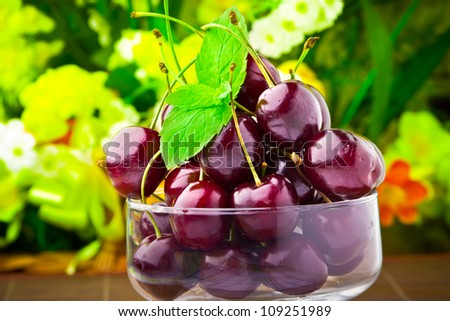 Sweet cherry fruits in glass goblet with mint leaf - stock photo