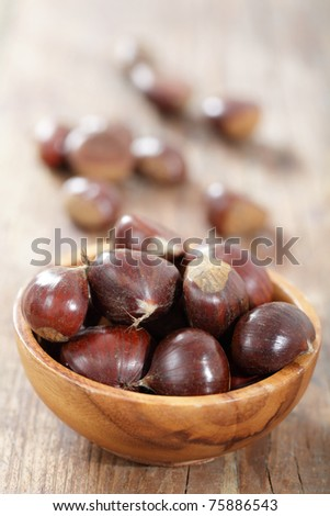 Sweet chestnuts in the wooden bowl on the rustic table - stock photo