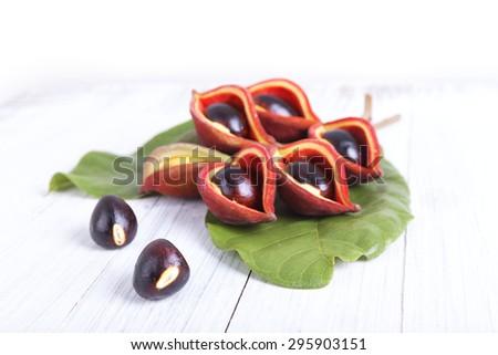 sweet chestnuts (Sterculia monosperma) on wooden background - stock photo
