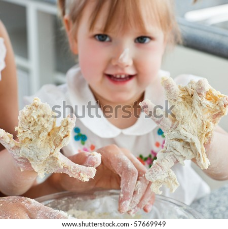 Sweet child baking cookies with hands in the kitchen - stock photo
