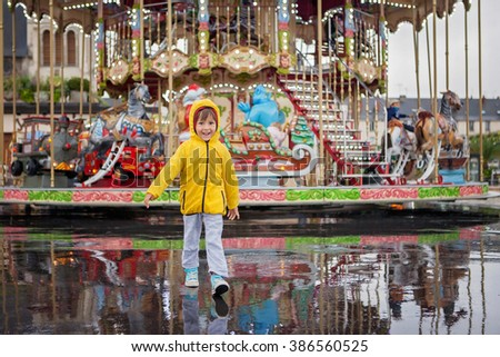 Sweet child, boy watching carousel in the rain, wearing yellow raincoat, summertime, reflection on the wet ground - stock photo