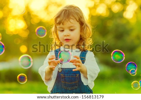 Sweet child child trying to catch soap bubble - stock photo