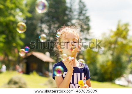 Sweet child playing with soap bubble - stock photo