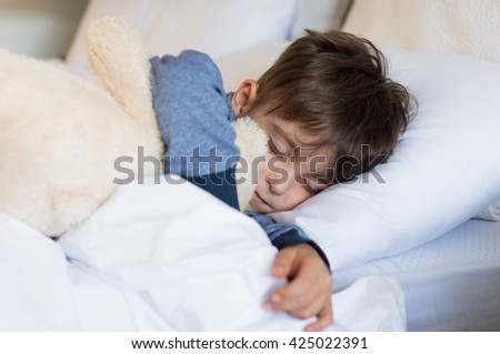 Sweet child sleeping in bed with his teddy bear. Little boy eyes closed lying in his bed for the afternoon nap. Cute little boy sleeping and dreaming in his white bed with toy.