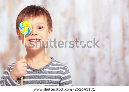 Sweet childhood. Portrait of an adorable little boy covering his eye with a lollipop with happy face expression - stock photo