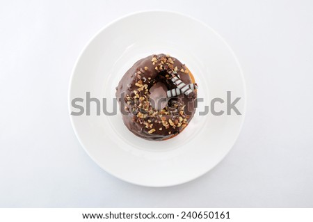 sweet chocolate almond cake doughnut on a plate white background - stock photo