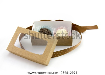 Sweet chocolate and coconut candies inside brown gift box made of carton paper - stock photo