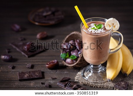 Sweet chocolate banana smoothie with coconut milk and dates decorated with mint leaves on wooden background - stock photo